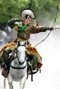 An archer in ancient samurai warrior uniform ridin